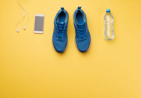 A studio shot of running shoes and smartphone on yellow background. Flat lay.