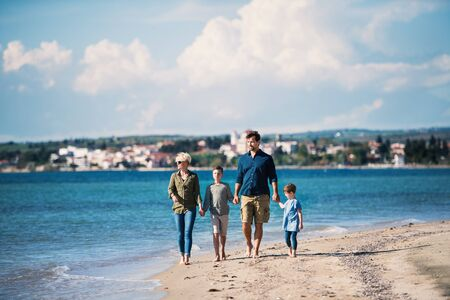 Young family with two small children walking outdoors on beach.