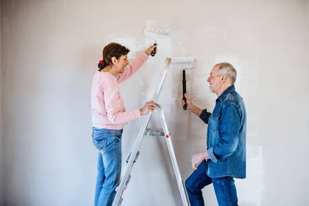 Senior couple painting walls in new home, relocation concept. Foto de archivo - 124677404