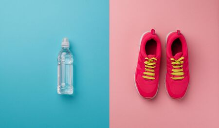 Studio shot of running shoes and water bottle on color background. Flat lay.