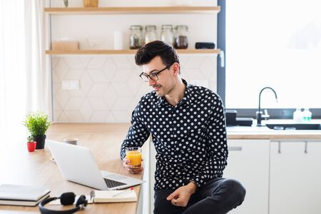 Young man with laptop sitting in kitchen, a home office concept.