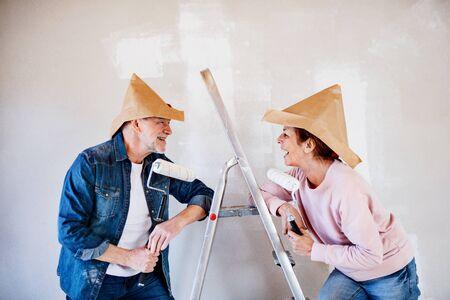 Senior couple painting walls in new home, having fun. Relocation concept. Foto de archivo - 124677653