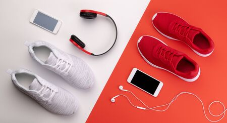 A studio shot of running shoes, smartphone and headphones on color background.