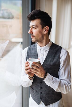 Young man with coffee standing by the window. Copy space. Stock Photo