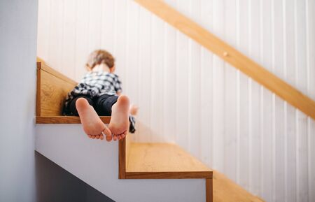 A rear view of small girl lying down on staircase. Copy space. Foto de archivo