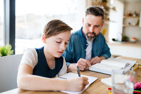 Mature father with small son sitting at table indoors, making homework.