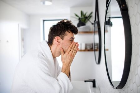 Young man washing face in the bathroom in the morning, daily routine.