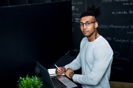 Young businessman with laptop in office, working.