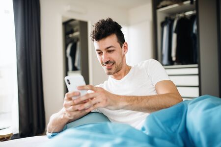 Young man with smartphone in bed at home, text messaging. 版權商用圖片