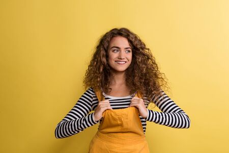Portrait of a young woman in a studio on a yellow background.