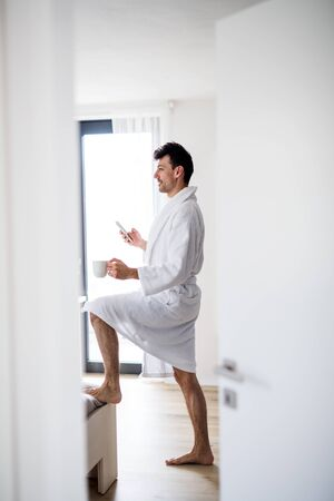 Young man with smartphone and coffee in the bedroom in the morning.