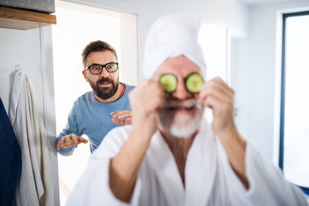 An adult hipster son and senior father in bathroom indoors at home, having fun.