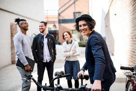 A happy young business people with bicycle standing outdoors. Imagens - 124984014