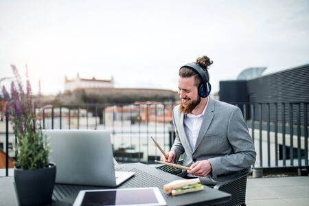 A young businessman with headphones sitting on a terrace, having fun.