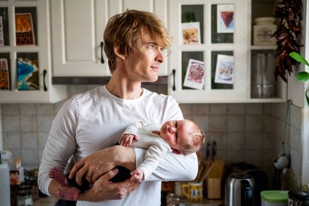Young father holding a newborn baby in kitchen at home.