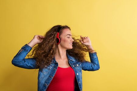 Portrait of a young woman with headphones in a studio on a yellow background.