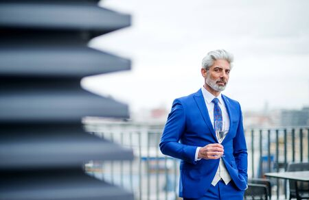A mature businessman with glass on a party outdoors on roof terrace in city.