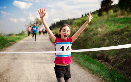 Corredor de niña pequeña cruzando la línea de meta en una competencia de carrera en la naturaleza.