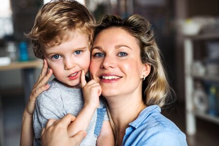 A happy mother with a toddler son indoors at home. Copy space. Stock Photo