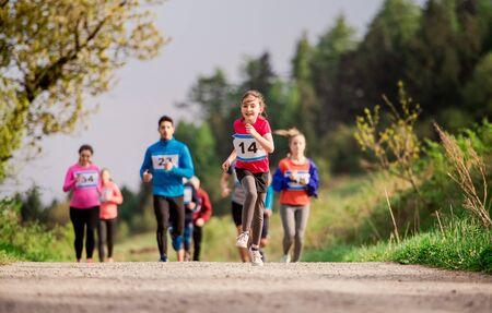 Große Gruppe von Menschen mit mehreren Generationen, die einen Rennwettbewerb in der Natur durchführen. Standard-Bild
