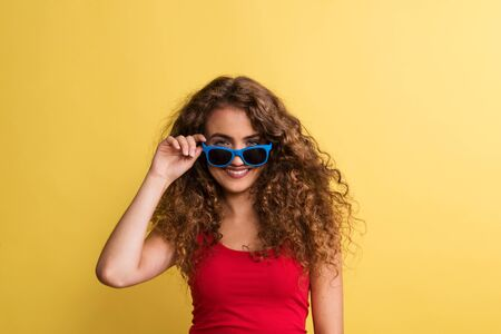 Portrait of a young woman with sunglasses in a studio on a yellow background.
