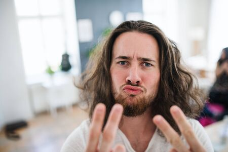 A portrait of young man with long hair indoors, fingers forming V for victory.