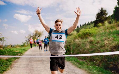 Corredor joven que cruza la línea de meta en una competición de carreras en la naturaleza. Foto de archivo