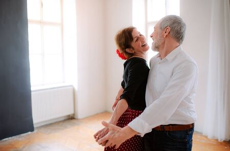 Senior couple attending dancing class in community center.