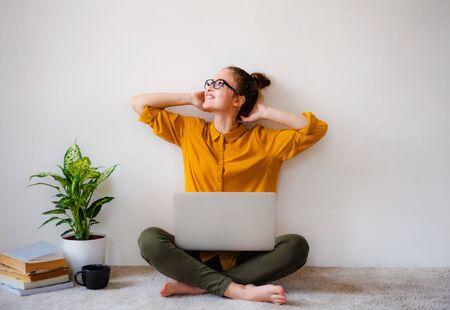 Une jeune étudiante assise sur le sol à l'aide d'un ordinateur portable pendant ses études. Banque d'images