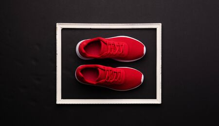 A studio shot of pair of running shoes on black background. Flat lay.