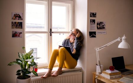 A young female student with an exercise book sitting on window sill, studying.