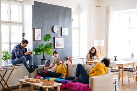 A group of young friends relaxing indoors, house sharing concept.