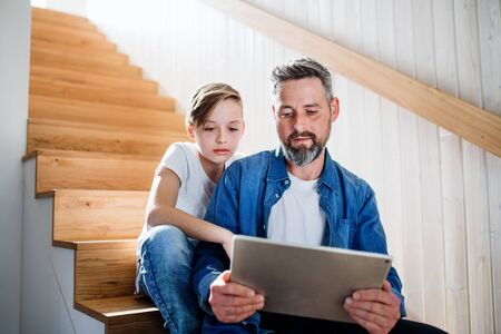 Mature father with small son sitting on the stairs indoors, using tablet.