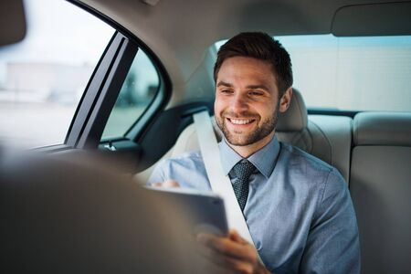Geschäftsmann mit Tablet auf den Rücksitzen im Auto sitzend, arbeiten.