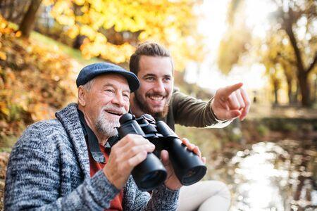 Padre mayor y su hijo con binoculares y en la naturaleza, hablando.
