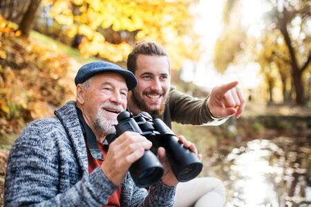 Senior father and his son with binoculars and in nature, talking.