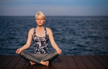 A portrait of young sportswoman doing yoga exercise on beach. Copy space. Stock Photo - 128518253
