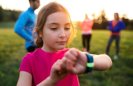 A portrait of small girl with large group of people doing exercise in nature.