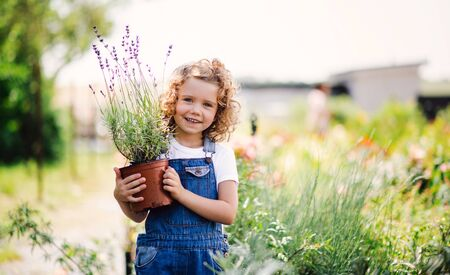 Portrait of small girl standing in the backyard garden, holding a plant in a pot.