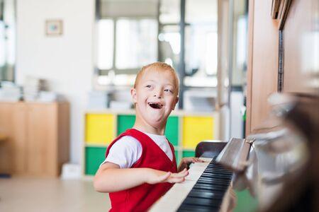 Een schooljongen met het syndroom van down die op school zit en piano speelt.