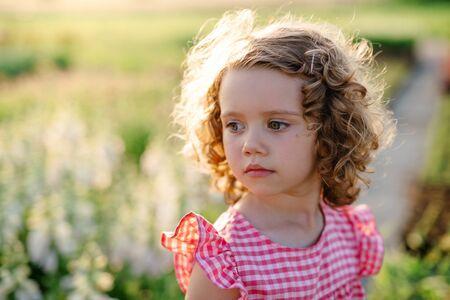 Portrait of small girl standing in the backyard garden. Standard-Bild