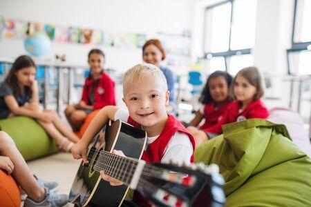 Een jongen met het syndroom van down met schoolkinderen en een leraar die in de klas zit en gitaar speelt.