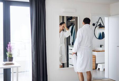 Jeune homme regardant dans le miroir dans la chambre le matin, routine quotidienne.