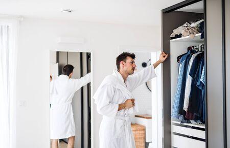 Ein junger Mann im Schlafzimmer am Morgen, der entscheidet, welche Kleidung er tragen soll. Standard-Bild