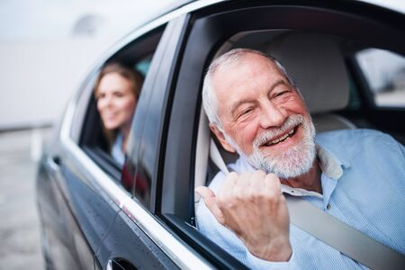 Senior man and young woman sitting in car, looking out of window. Imagens