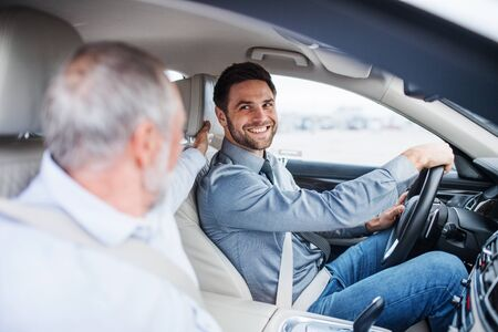 Father and son sitting in car, driving and talking. Imagens