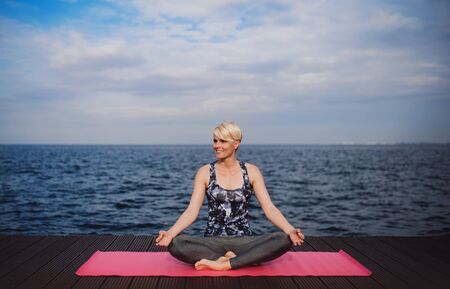 A portrait of young sportswoman doing yoga exercise on beach. Copy space.