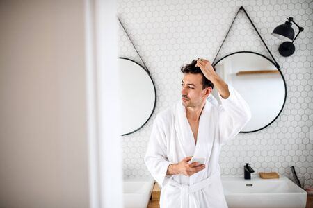 Young man with smartphone in the bathroom in the morning. Stock fotó