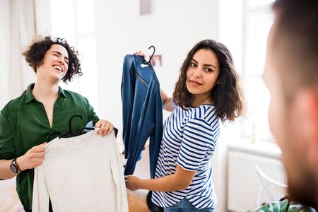 A group of young friends with clothes indoors, house sharing concept. Stock Photo