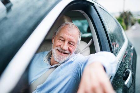 Happy senior man sitting in car in driver seat. Imagens